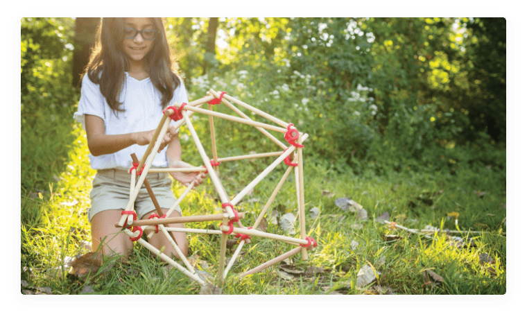 Young girl creating a polyhedron with wooden sticks